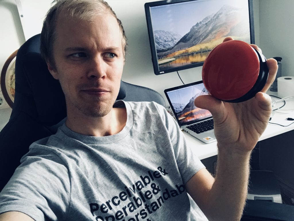 The author Hampus looking suspiciously at a red, round button in his hand