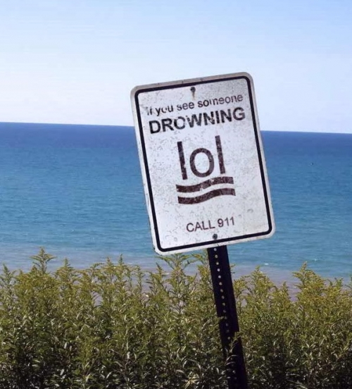 A sign at a cliff stating: if you see someone drowning, call 911